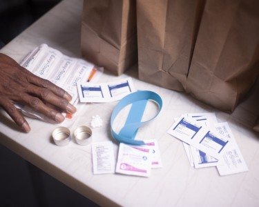 A hand gesturing towards Syringe Service supplies including alcohol wipes, tourniquet, cookers, and syringes.